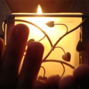 hands touch a candle holder in the dark