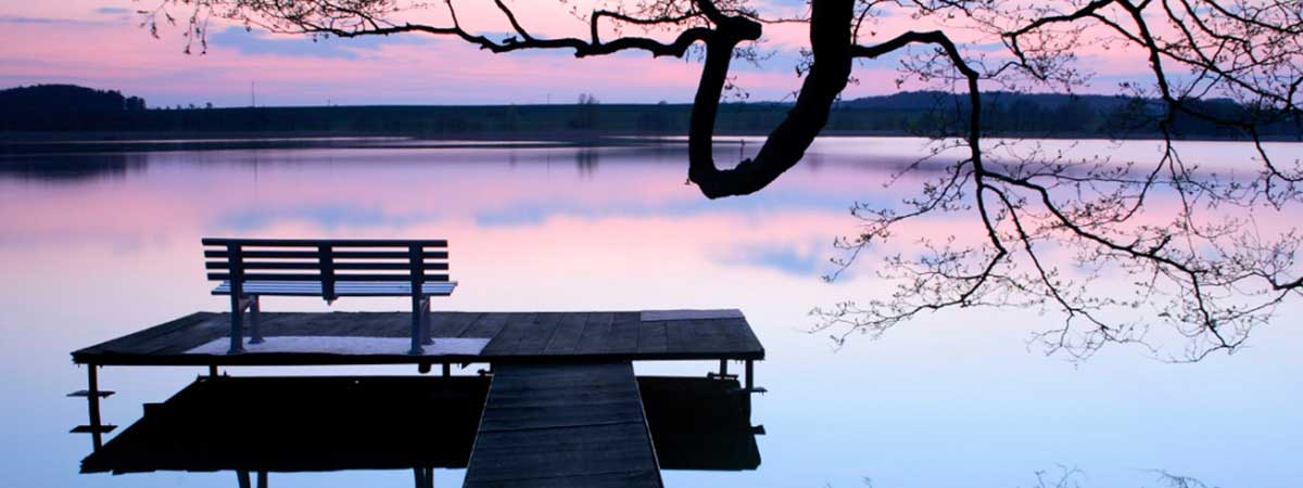 dock with bench overlooking lake in early evening