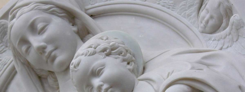 Detail of white marble sculpture depicting Madonna and Child faces