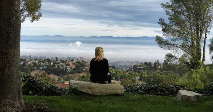 woman sitting on boulder looking out over the misty valley